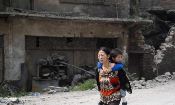 This photo taken on Sept. 8, 2012 shows a woman carrying her child on her back along a street in Yiliang after two quakes hit the area on the border of southwestern Yunnan and Guizhou provinces an hour apart around the middle of the day followed by a string of aftershocks. (STR/AFP/GettyImages)