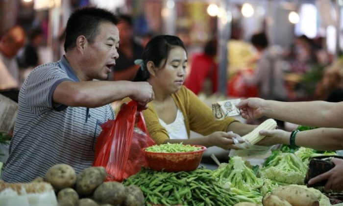 People buy vegetables at a market in Huaibei in eastern China's Anhui province on Sept. 9, 2012. Despite a gloomy economy, China's food prices are on the rise and causing stress among the common people. (STR/AFP/GettyImages)