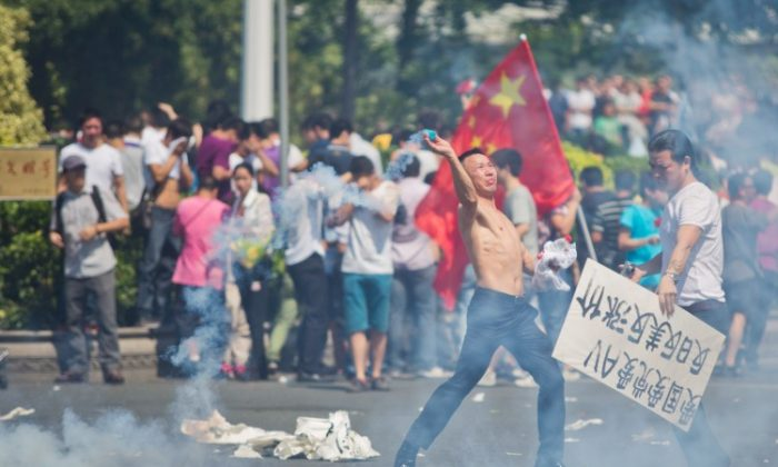 Anti-Japanese protester throws a gas cannister as they demonstrate over the disputed Senkaku Islands, on Sept. 16, 2012 in Shenzhen, China. Protests have taken place across China in a dispute that is becoming increasingly worrying for regional stability. (Lam Yik Fei/Getty Images)