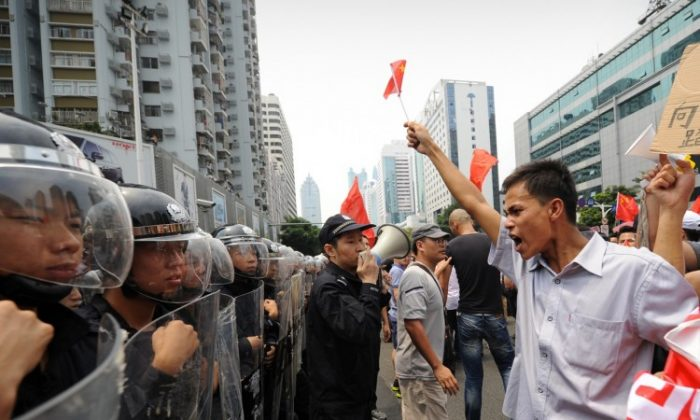 A line of riot police stand firm against anti-Japan protesters during a protest over the Diaoyu islands issue, known as the Senkaku islands in Japan, in the southern Chinese city of Shenzhen on Sept. 18, 2012. (Peter Parks/AFP/Getty Images)