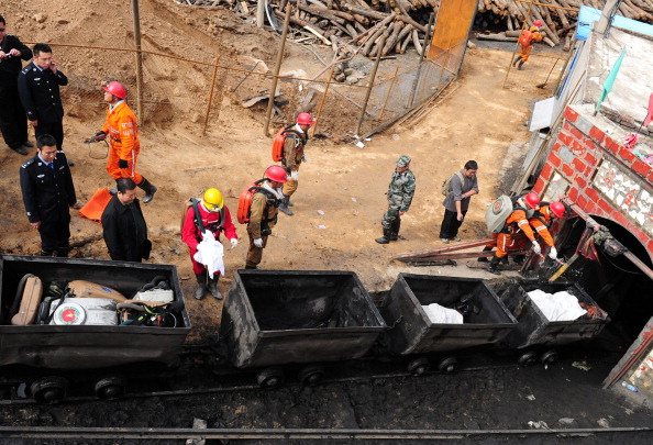 Chinese rescuers remove bodies of miners killed when the cable of a rail carriage taking workers into the mine snapped, sending the 34 miners plummeting into the pit, in Baiyin, located in China's Gansu Province on Sept. 25, 2012. (STR/AFP/GettyImages)