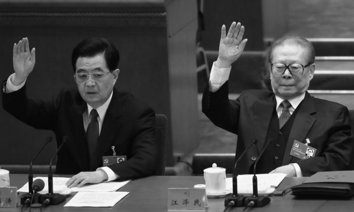 Former Chinese Communist Party head Hu Jintao and former Party head Jiang Zemin raise their hands during the closing session of the 18th Party Congress on Nov. 14, 2012, in Beijing. Hu visited Yancheng City, Jiangsuto deal with a Falun Gong matter in December, according to a source.(Feng Li/Getty Images)