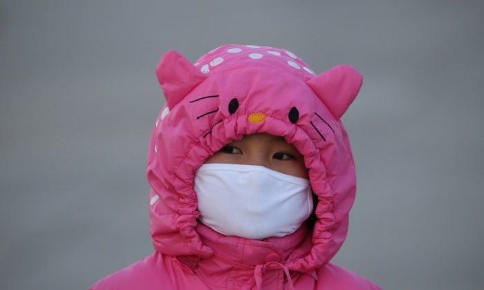 A girl wears a mask at the Tiananmen Square on Jan. 17, 2013 in Beijing to protect against air pollution. (Feng Li/Getty Images)