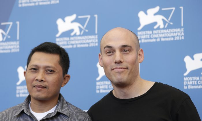 Actor Adi Rukun, left, and director Joshua Oppenheimer pose for photographers at the photo call for the film The Look of Silence the 71st edition of the Venice Film Festival in Venice, Italy, Thursday, Aug. 28, 2014. (AP Photo/David Azia)
