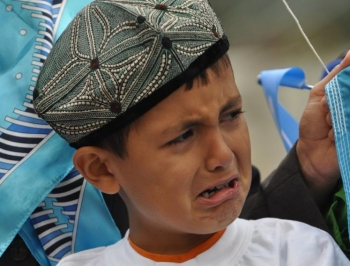 A young Uyghur boy in Calgary, Canada, cries at a rally to protest the Communist Party's suppression in Xinjiang, China. (Jerry Wu/The Epoch Times)