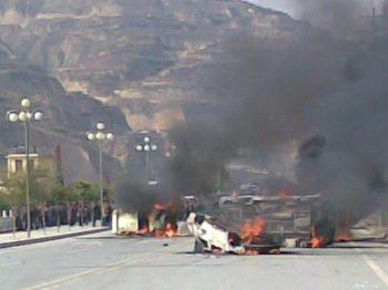 Burning vehicles block the road at the site of the riot.    (Photo provided by mainland China Internet surfer)