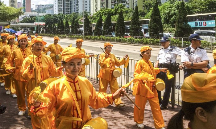 The Divine Land Marching Band, a waist drum troupe,  marches through the streets of Hong Kong to mark the Chinese Communist Party's sixteen year-long persecution of Falun Gong (Phillip Evich/Epoch Times)