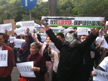Protesters in Panyu district of Guangzhou Province gather to protest local authorities. The sign reads 'Oppose trash incinerator, keep Panyu green!'