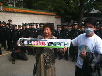 A woman protests in Panyu district of Guangzhou Province. The sign reads 'Oppose trash incinerator, keep Guangzhou green!'