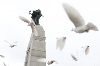 Sixty-five doves, one for every 10,000 Canadian soldier and support personnel who served in WWI, are released at the ceremony to honour these service men and women. The memorial consists of a granite archway with bronze angels on top symbolizing Peace and Freedom, and 22 bronze figures advancing through the arch representing the Canadians who served their country at war. (PMO photo by Jill Propp)