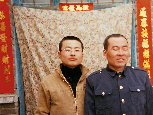 Li Lankui (R) stands with his son before his arrest