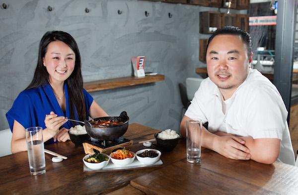 Chef Hooni Kim (R) shares his sundubu jjigae—Korean spicy tofu stew—with writer CiCi Li at  his Flatiron restaurant Hanjan. (Petr Svab/Epoch Times)
