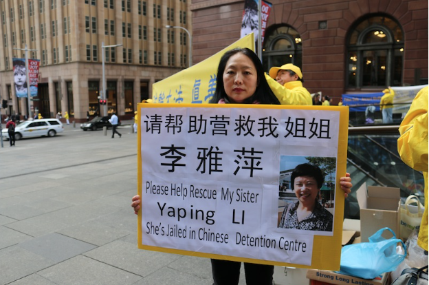 Mrs Ying Li holds a placard asking for the public's help to rescue her sister, Yaping Li, who was arrested five months ago for practising Falun Gong. (Melanie Sun/Epoch Times)