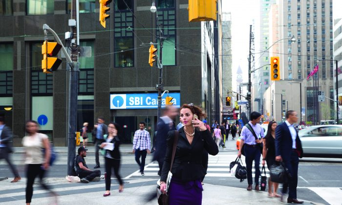 "A woman talks on a cellphone in downtown Toronto. The constant busyness inherent in today's work culture is taking an unhealthy toll, leading to a slowly growing ""anti-busy"" revolution. (Don Quincy/DQC Photo)"
