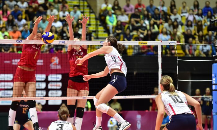 USA's Kelly Murphy's spike gets blocked by 199cm tall Xinyue Yuan of China during their FIVB World Grand Prix preliminary competition match at the Coliseum Hong Kong on Saturday July 18, 2015. China went on to win the game 15-12 in the 5th set. (Bill Cox/Epoch Times)