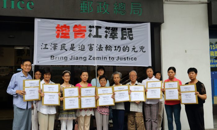 10 Hong Kong Falun Gong practitioners gather in front of the post office in Central before mailing their indictments and criminal complaints against Jiang Zemin to the Supreme People's Court and the Supreme People's Procuratorate on July 16. (EpochTimes)