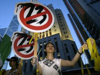 A girl hands out yellow ribbons against the controversial Article 23 law during a protest 09 July 2003. (Peter Parks/AFP/Getty Images)