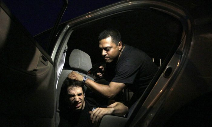 Two men participate in a kidnapping drill at the School of Personal Protection in an intensive self-defense course in Caracas, Venezuela, May 30, 2012. (AP Photo/Fernando Llano)