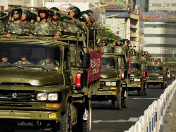 Chinese paramilitary police trucks drive down a main street in downtown Urumqi. Riot police and soldiers kept a strong presence in China's Urumqi city on July 9 after days of bloodshed. (Peter Parks/Getty Images)