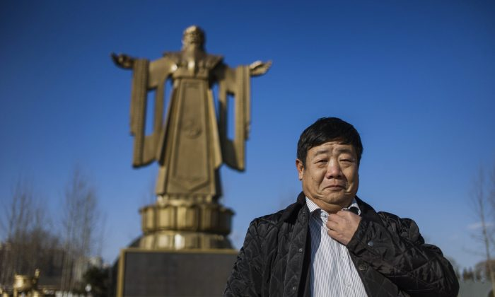 Former Chinese general Wang Dianming posing next to a Confucius statue in the seaside resort in Beidaihe, Hebei province. (FRED DUFOUR/AFP/Getty Images)