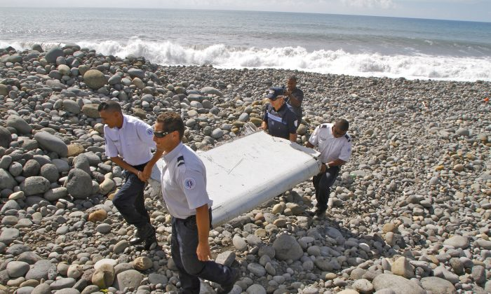 French police officers carry a piece of debris from a plane in Saint-Andre, Reunion Island on Wednesday, July 29, 2015. (AP Photo/Lucas Marie)