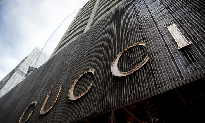 This picture taken on April 23, 2013 shows Chinese mainland tourists sitting outside a Gucci store in Hong Kong. The dazzling display of wealth highlights the booming high-end goods sector driven by cashed-up Chinese who turned swathes of Hong Kong into their luxury shopping playgrounds, as they shop in Hong Kong to avoid China's high taxes. AFP PHOTO / ANTHONY WALLACE (ANTHONY WALLACE/AFP/Getty Images)