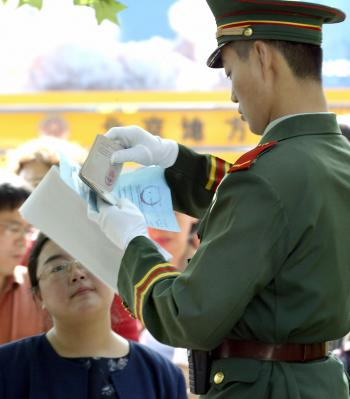 CONTROL: A Chinese paramilitary guard checks the passport of a U.S. visa applicant as she arrives for her appointment to submit her application at the U.S. Embassy in Beijing on May 17, 2004. (Goh Chai Hin/Getty Images )