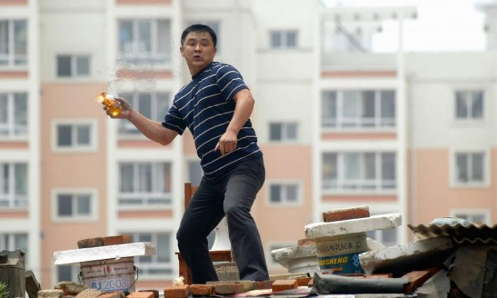 A Chinese man standing on his roof hurls a Molotov cocktail as he fights to keep his home from being demolished on July 14, 2005, in Shenyang of Liaoning Province. (China Photos/Getty Images)