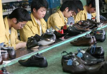 Factory workers check shoes for flaws on a production line at the Kangnai shoe factory in the Chinese city of Wenzhou. (Mark Ralston/AFP/Getty Images)