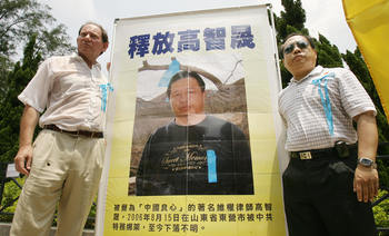 Edward McMillan-Scott (L) Vice President, European Parliament poses for pictures with Democracy Legislator Albert Ho next to a portrait of mainland jailed human rights lawyer Gao Zhisheng in Hong Kong, in 2006.  (Mike Clarke/AFP/Getty Images)