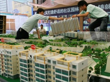 Two workers move a building model during a real estate fair in 2007 in Xian of Shaanxi Province, China. According to statistics recently, rental prices for apartments went up by 15 percent in Beijing from 2010 to 2011, 10 percent in Shanghai, and 20 percent in Guangzhou. (China Photos/Getty Images)