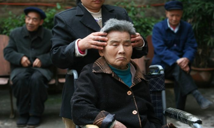An attendant gives massage to a senior citizen in an elder care center on Oct. 16, 2007 in Chongqing, China. (China Photos/Getty Images)