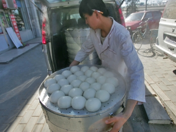 A worker loads steamed buns onto a truck in March of 2008 in Beijing, China. Recently, the Shanghai Shenglu Food Company was shut down due to chemicals that were found inside the company's steamed buns. (China Photos/Getty Images)
