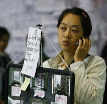 A lady promoting her apartment in the Autumn Real Estate Show in southwest China's Chongqing city on October 24. (GETTY IMAGES)