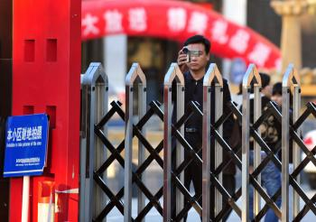 Foreign journalists are filmed by a plainclothed security personnel behind a entrance gate to Bobo Freedom Village where Chinese dissident Zeng Jinyan lives under unofficial house arrestin Beijing.  (Frederic J Brown/AFP/Getty Images )