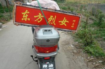 A young man plans to support Deng Yujiao by traveling one thousand kilometers on a scooter to give her a plaque engraved Lady of Integrity.(The Epoch Times)