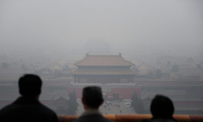 Tourists take in the view of the Forbidden City from atop Coal Hill in Jingshan Park, north of the former imperial palace on a smoggy day in Beijing on Dec. 10, 2009. (Frederic J. Brown/AFP/Getty Images)