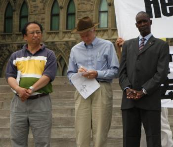 (L-R) Speakers Li Xun, president of Falun Dafa Association of Canada; Hon. David Kilgour, former MP and Secretary of State for Asia-Pacific; and Francis Yel of the South Sudan-Canada Association at the rally on Parliament Hill in Ottawa on July 18, 2010, marking 11 years since the start of the persecution of Falun Gong in China. (Donne He/The Epoch Times)
