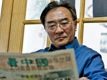 OTHER SHORE: Sitting in a small office in Flushing, Zhang Kaichen reads one of the newspapers produced by the Chinese dissident community. He now works a menial job and barely gets by, but in China, as a propaganda director, he had his own office and regularly received bribes. (Matthew Robertson/The Epoch Times)