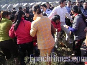 A scene of conflict—police beating villagers. (The Epoch Times)