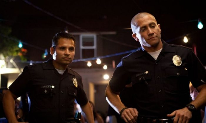 Jake Gyllenhaal (R) and Michael Peña (L) as police officer partners who are marked for death after confiscating money and firearms from a cartel in the dramatic mystery 'End of Watch.' (Scott Garfield/ Open Road Films)