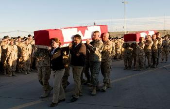 Diplomats and soldiers carrying the casket of Calgary Herald reporter Michelle Lang are followed by troops carrying the caskets of four comrades on Jan. 1, 2010. The five Canadians were slain two days earlier in Kandahar, Afghanistan. (Sgt. Gemma Bibby of the Royal Air Force, DND)