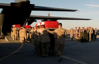 Pallbearers carry the caskets of slain Canadian journalist Michelle Lang and four fallen Canadian soldiers into a military aircraft on Jan. 1, 2010, to return them to Canada.  (Sgt. Gemma Bibby of the Royal Air Force, DND)