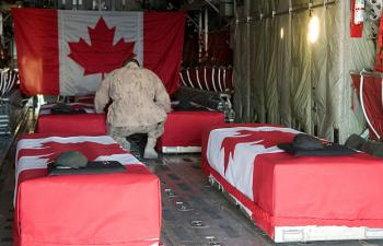 A Canadian soldier bids farewell in a military transport aircraft on Jan. 1, 2010, before his four fallen comrades and journalist Michelle Lang are flown back to Canada. (Sgt. Gemma Bibby of the Royal Air Force, DND)