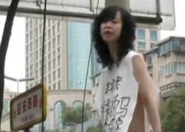 A naked woman with a piece of white cloth hanging off of her shoulders stood on a garbage bin outside the Supreme Court of Guizhou Province. (the original video with Chinese text is two minutes, 35 seconds; a shorter, 1 minute 38 second version has been uploaded with this article)