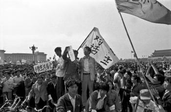 May 14th, 5pm: Flags in the Tiananmen Square declare: 'Democratic dialogue'. At this time the actual dialogue between the regime and students are not broadcas on TV as the regime had promised. One professor pleads: 'save my students'. Behind him a banner says: 'Teachers and students will live or die together'.