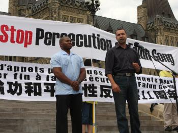 Rev. Majed El Shafie, president of One Free World International, speaks on Parliament Hill in Ottawa on July 18 at a rally to call on the Canadian government to help stop the persecution of Falun Gong in China. On the left is Pastor Lyle Notice of the Ottawa Seventh-day Adventist Church. (Donna He/The Epoch Times)