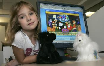 A child poses next to her Webkinz plush pets and a computer screen displaying the Webkinz website, which features  an online community where kids care for their toy pets' virtual twin. The commercial social network site targets elementary school children and is even popular with pre-schoolers. (Nicholas Kamm/AFP/Getty Images)