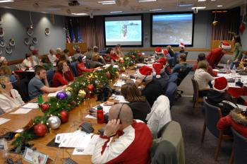 Military and civilian volunteers answer phone calls and emails from children wanting to know Santa's whereabouts on Christmas Eve, 2007, at the NORAD Tracks Santa Operations Center at Peterson Air Force Base in Colorado. NORAD Tracks Santa celebrated its 50th year in 2008. (NORAD and USNORTHCOM Public Affairs)