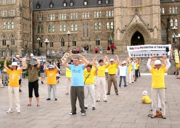 Falun Gong practitioners perform the Falun Standing Stance on Parliament Hill in Ottawa on July 18, 2010. It is the second of five meditative exercises of the Falun Gong cultivation system, and consists of four wheel-holding positions. (The Epoch Times)